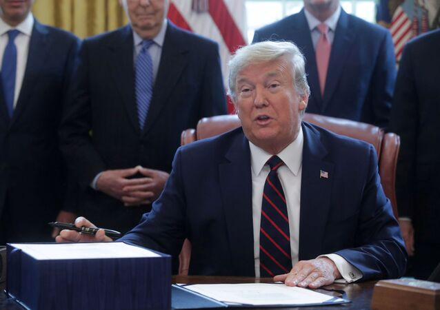 U.S. President Donald Trump hosts a signing ceremony for the $2.3 trillion coronavirus aid package bill in the Oval Office of the White House in Washington, U.S., March 27, 2020