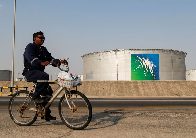 An employee rides a bicycle next to oil tanks at Saudi Aramco oil facility in Abqaiq, Saudi Arabia October 12, 2019.