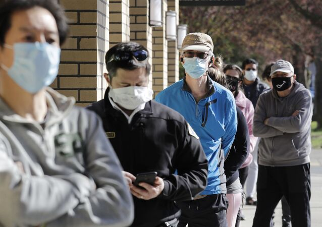 Customers wear a variety of protective masks as they wait some six-feet apart to enter a Trader Joe's store, where the number of customers allowed inside at any one time was limited because of the coronavirus outbreak, Wednesday, April 8, 2020, in Seattle