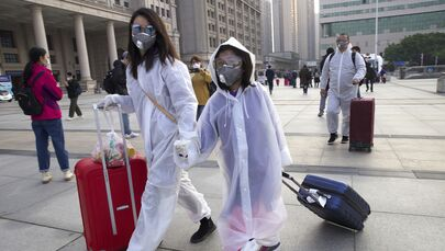 Passengers wearing face masks and rain coats to protect against the spread of coronavirus walk outside of Hankou train station after of the resumption of train services in Wuhan in central China's Hubei Province, Wednesday, 8 April 2020. After 11 weeks of lockdown, the first train departed Wednesday morning from a re-opened Wuhan, the origin point for the coronavirus pandemic, as residents once again were allowed to travel in and out of the sprawling central Chinese city.