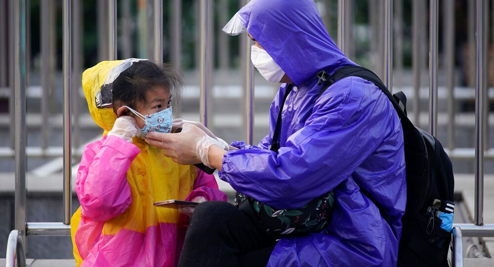 A person helps a child put on a protective face mask at Wuhan's Hankou Railway Station