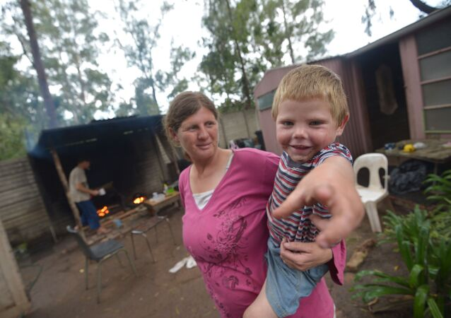 Marinda Labuschagne and her boy stand in front of their home with her husband cooking in the kitchen on a wood fire at a squatter camp for poor white South Africans at Coronation Park in Krugersdorp, on December 12, 2013