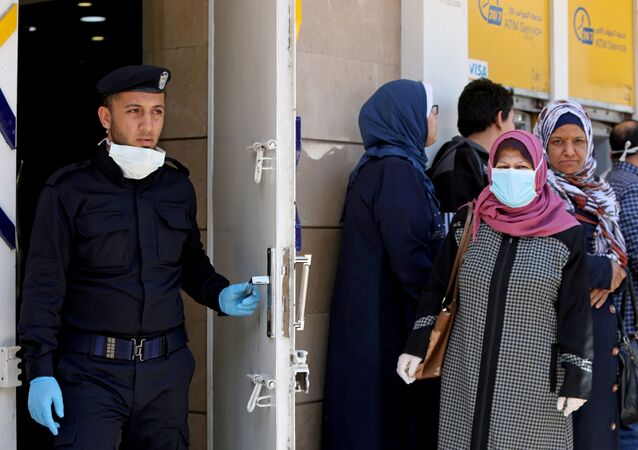 A Palestinian policeman stands guard as a woman, wearing a mask as a precaution against the the coronavirus disease (COVID-19), waits with other people outside a bank to withdraw cash, in Gaza City March 29, 2020