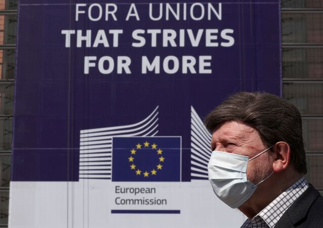 A man wearing a face mask walks past the European Commission headquarters as the spread of coronavirus disease (COVID-19) continues in Brussels, Belgium April 9, 2020.