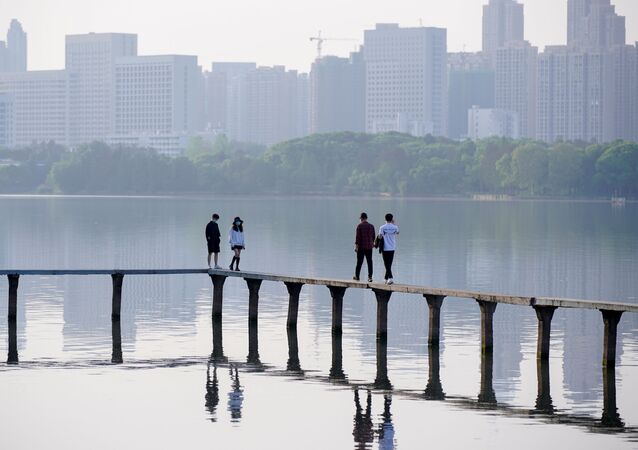 People wearing face masks, walk along the East Lake after lockdown in Wuhan, the epicentre of China's novel coronavirus disease (COVID-19) outbreak, is lifted, in Wuhan, Hubei province, China, April 9, 2020