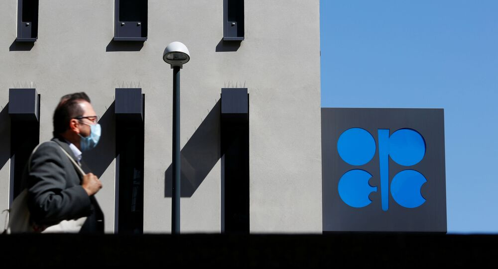 A person passes the logo of the Organization of the Petroleoum Exporting Countries (OPEC) in front of OPEC's headquarters in Vienna, Austria April 9, 2020