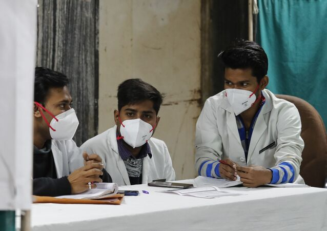 Indian doctors wait in an area set aside for possible COVID-19 patients at a free screening camp at a government run homeopathic hospital in New Delhi, India, Friday, March 13, 2020