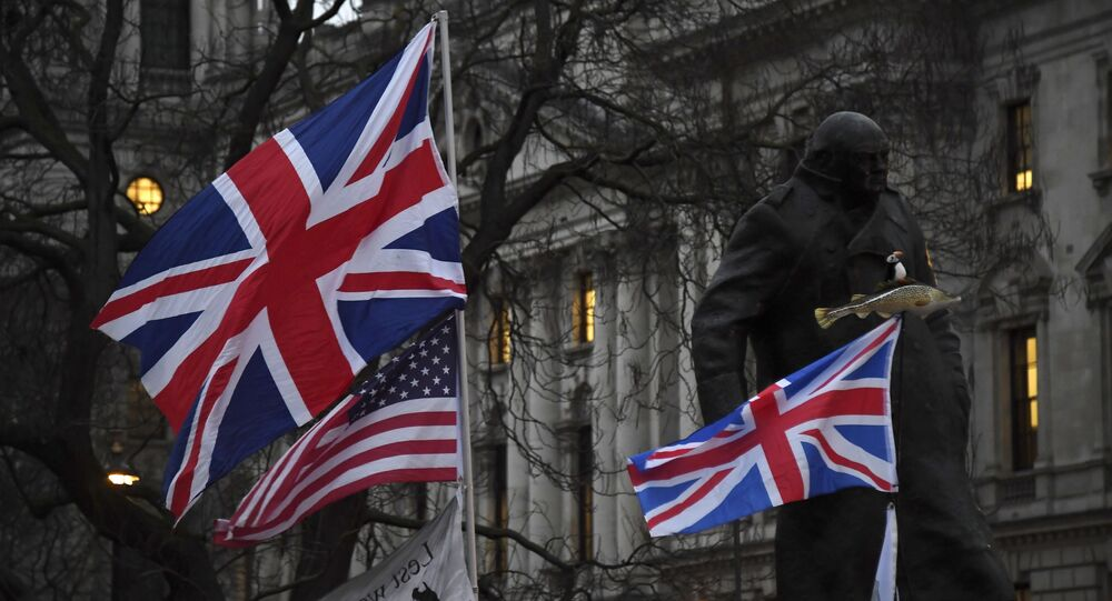 Brexit supporters hold British and US flags in front of the Statue of Winston Churchill during a rally in London, Friday, Jan. 31, 2020