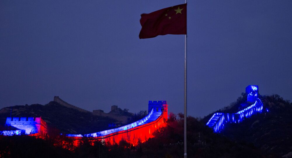 The Chinese national flag flies near a section of the Great Wall of China prepared to be lit by blue light to commemorate the 70th anniversary of the United Nations on the outskirts of Beijing, China, Saturday, Oct. 24, 2015. More than 200 iconic monuments, buildings, museums, bridges and other landmarks around the world were lighted up with blue - the official color of the United Nations to mark its 70th anniversary.