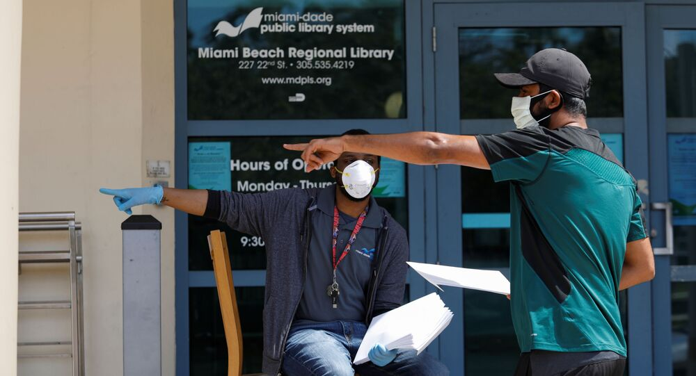 A man speaks with a library worker after receiving an unemployment form, as the outbreak of coronavirus disease (COVID-19) continues, in Miami Beach, Florida, U.S., April 8, 2020
