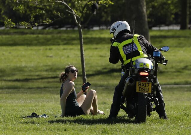 A woman is told to go home by a police officer on a motorbike to stop the spread of coronavirus and keep the park open for people observing the British government's guidance of social distancing, only using parks for dog walking, one form of exercise a day, like a run, walk, or cycle alone or with members of the same household, on Primrose Hill in London, Sunday, April 5, 2020.