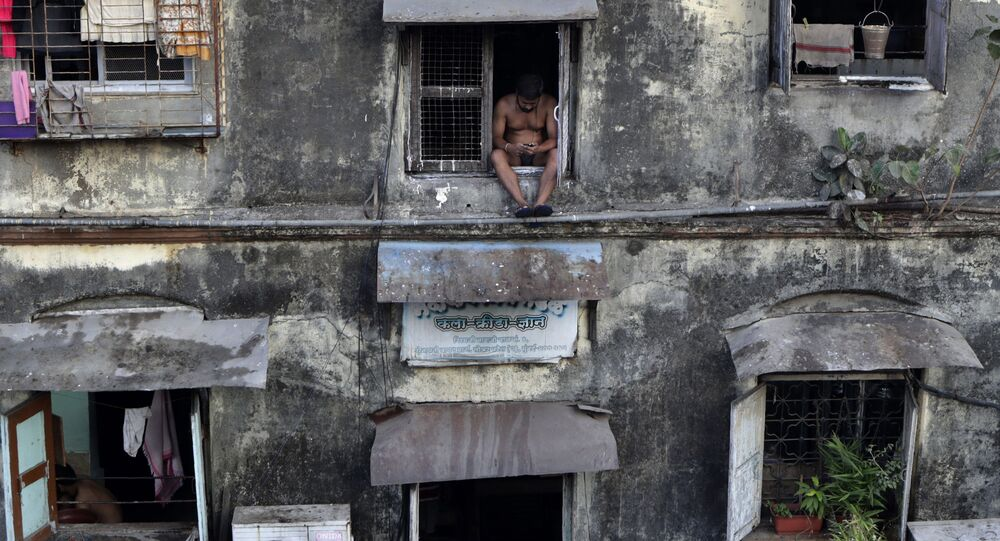 A man sits alone at the window of a Chawl during a lockdown to prevent the spread of the new coronavirus at Lower Parel area in Mumbai, India, Sunday, April 5, 2020.