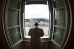This handout photo taken on March 29, 2020 and released by the Vatican press office, the Vatican Media, shows Pope Francis praying from the window of the Apostolic Palace overlooking an empty St. Peter' Square after his livestreamed the Angelus prayer on March 29, 2020 at the Vatican.