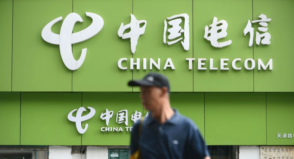 In this file a man walks past a China Telecom store in Wuhan, in central China's Hubei province on August 21, 2013.