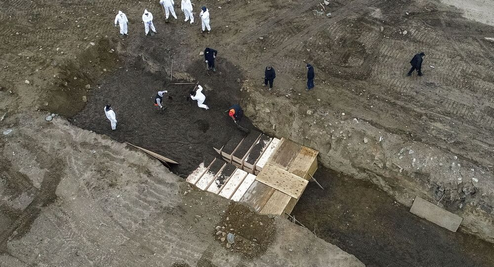 Workers wearing personal protective equipment bury bodies in a trench on Hart Island, Thursday, April 9, 2020, in the Bronx borough of New York. On Thursday, New York City's medical examiner confirmed that the city has shortened the amount of time it will hold on to remains to 14 days from 30 days before they will be transferred for temporary internment at a City Cemetery. Earlier in the week, Mayor Bill DeBlasio said that officials have explored the possibility of temporary burials on Hart Island, a strip of land in Long Island Sound that has long served as the city's potter's field.