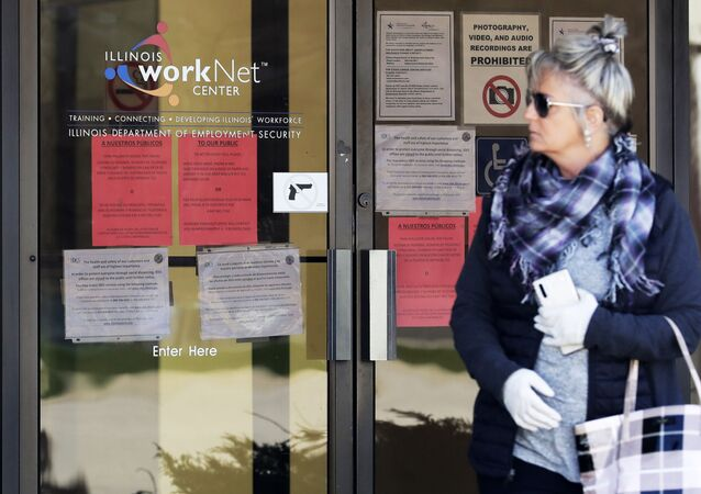 A woman looks to get information about job application in front of IDES (Illinois Department of Employment Security) WorkNet center in Arlington Heights, Ill., Thursday, 9 April 2020. Another 6.6 million people filed for unemployment benefits last week, according to the US Department of Labour, as American workers continue to suffer from devastating job losses, furloughs and reduced hours during the coronavirus pandemic.
