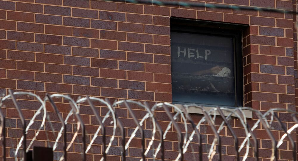 Signs made by prisoners pleading for help are seen in a window of Cook County Jail in Chicago, Illinois, U.S., April 9, 2020 amid the coronavirus disease (COVID-19) outbreak