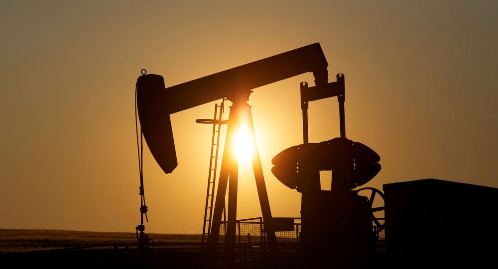 An oil pump jack pumps oil in a field near Calgary, Alberta, Canada on July 21, 2014