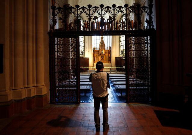 A worker stands outside a chapel set with hospital beds inside the Cathedral Church of St. John the Divine for what will be a temporary field hospital constructed by the Samaritan's Purse and Mount Sinai Hospital on Manhattan's Upper West Side during the outbreak of the coronavirus disease (COVID19) in New York City, New York, U.S., April 8, 2020