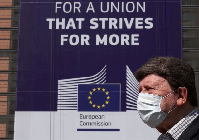 FILE PHOTO: A man wearing a face mask walks past the European Commission headquarters as the spread of coronavirus disease (COVID-19) continues in Brussels, Belgium April 9, 2020.
