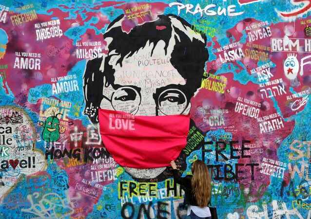 A woman wearing a face mask touches the graffiti-covered John Lennon Wall as the spread of the coronavirus disease (COVID-19) continues in Prague, Czech Republic, 6 April 2020.