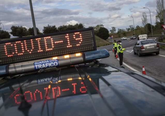 Spanish Civil Guard officers stop cars at a checkpoint as the lockdown to combat the spread of coronavirus continues, near San Sebastian de los Reyes, outskirts of Madrid, Spain, Tuesday, April 7, 2020.