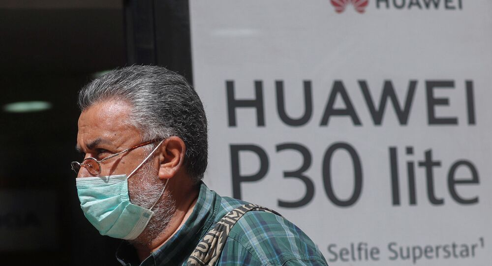 A man, wearing a protective mask due to the spread of coronavirus disease (COVID-19), walks past a Huawei store in Cairo, Egypt March 31, 2020.