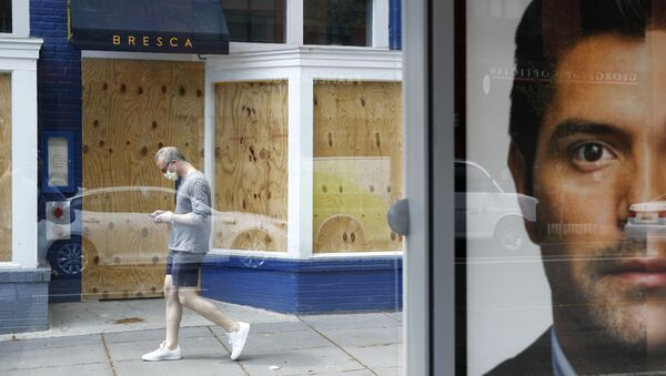 A man wearing a face mask to protect against the spread of the new coronavirus walks past a boarded-up restaurant in Washington, Thursday, April 9, 2020. - Sputnik International