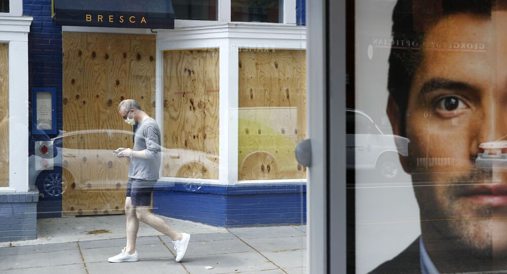 A man wearing a face mask to protect against the spread of the new coronavirus walks past a boarded-up restaurant in Washington, Thursday, April 9, 2020.