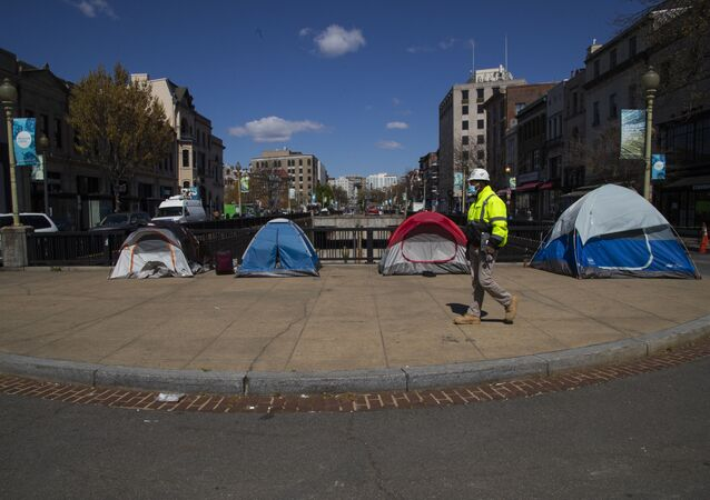 A street maintenance subcontractor for the District of Columbia walks past tents set up by the homeless on a sidewalk in Washington's Dupont Circle.