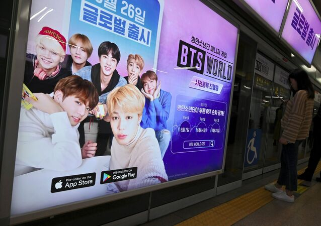 Passengers stand next to an advertisement for the role-playing game BTS World at a subway station in Seoul on June 25, 2019.