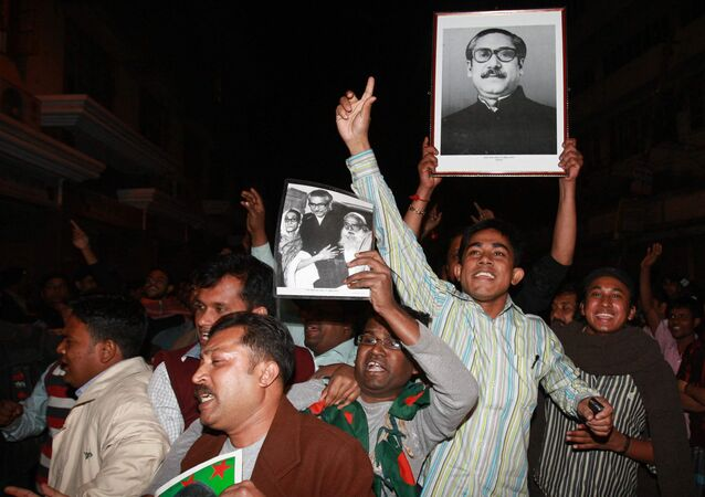Cheering supporters carry a portrait of the country's independence leader Sheikh Mujibur Rahman outside the Dhaka central jail  in Dhaka, Bangladesh, early Thursday, Jan. 28, 2010.