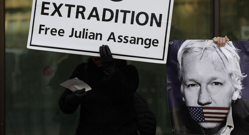 Protesters hold banners outside Westminster Magistrates Court in London, where Julian Assange is due to appear, Monday, Jan. 13, 2020.