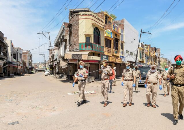 Punjab police personnel wearing facemasks patrol on a deserted street during a government-imposed nationwide lockdown as a preventive measure against the COVID-19 coronavirus, in Amritsar on April 11, 2020.