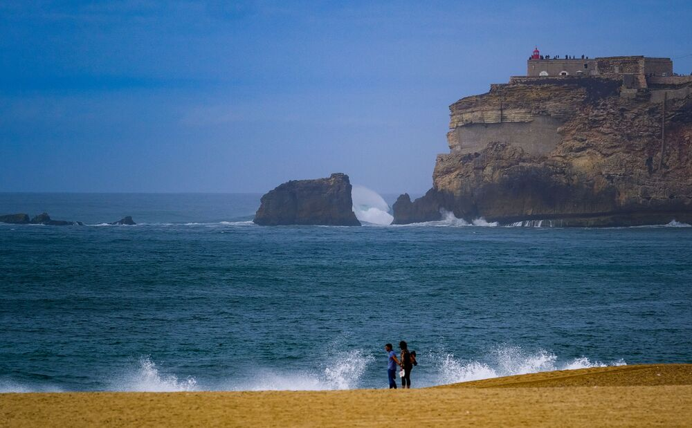 A lighthouse is seen on the beach in Nazare, Portugal. The town of Nazare on the Portuguese coast has become a cult place. Lovers of tickling nerves flock here: some in attempts to ride the largest wave in the world.