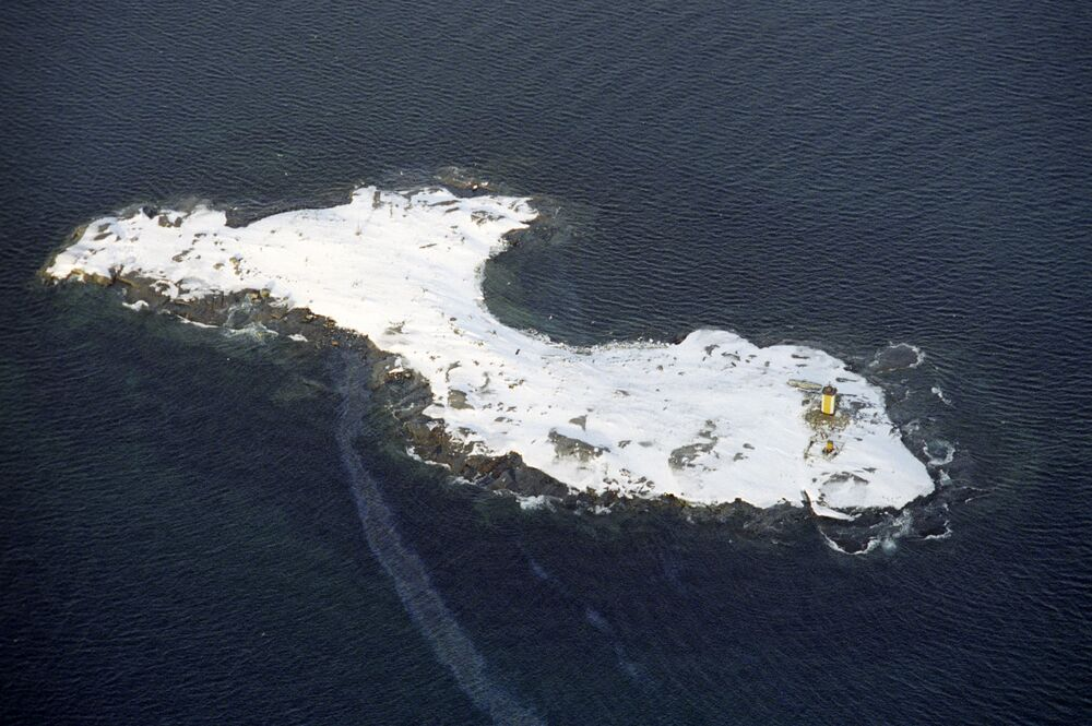 An island with a lighthouse in the Barents Sea beyond the Arctic Circle. Helicopter shot.