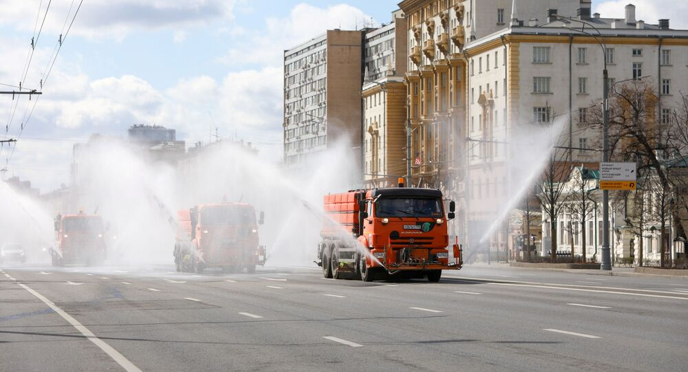 Vehicles drive near the U.S. embassy and spray disinfectant while sanitizing a road to prevent the spread of the coronavirus disease (COVID-19) in Moscow, Russia April 12, 2020