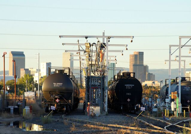Oil tanker railcars are parked at a filling rack at sunrise with the Denver downtown skyline in the background October 14, 2014