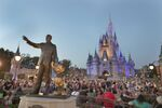 In this Wednesday, Jan. 15, 2020 photo, a statue of Walt Disney and Mickey Mouse is seen in front of the Cinderella Castle at the Magic Kingdom theme park at Walt Disney World in Lake Buena Vista, Fla. Florida tourism officials say cases of the new coronavirus are having little visible impact on the theme park industry so far.