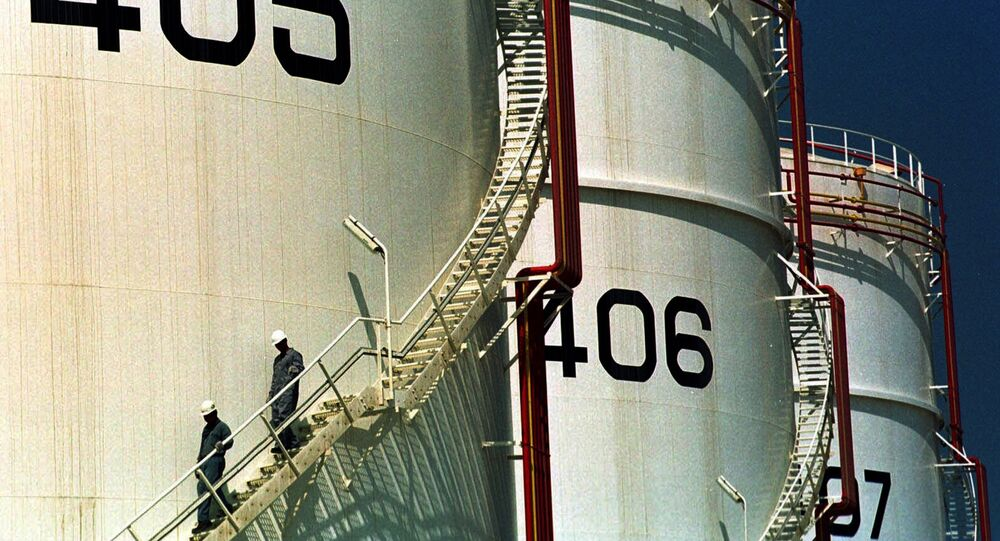 In this Monday, September 25, 2000 file photo, two workers climb down from one of the tanks in an oil tank-farm in Jebel Ali, 25 miles (40 kms.) south of Dubai in the United Arab Emirates.