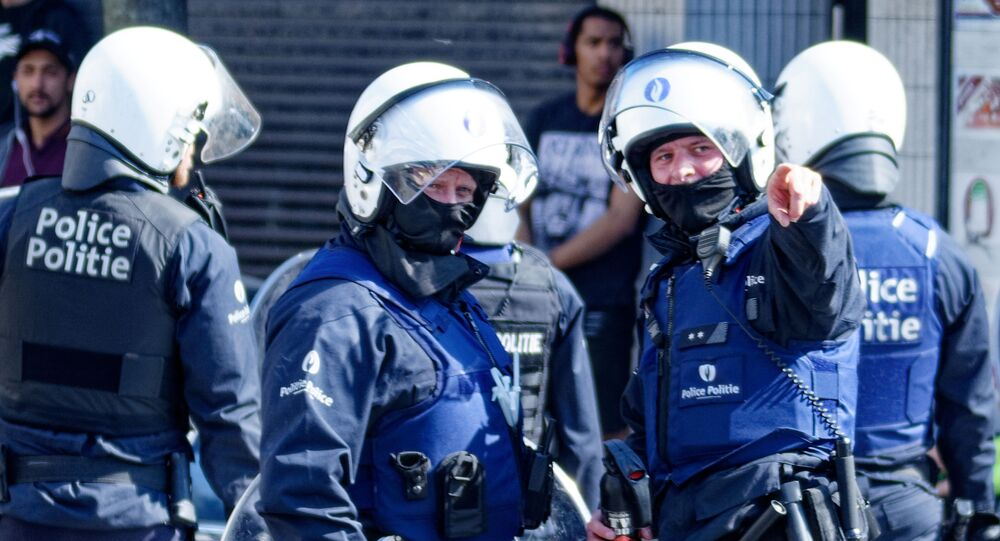 Belgian police officers wearing protective gears stand at the site of unrests in Anderlecht, Brussels, on April 11, 2020