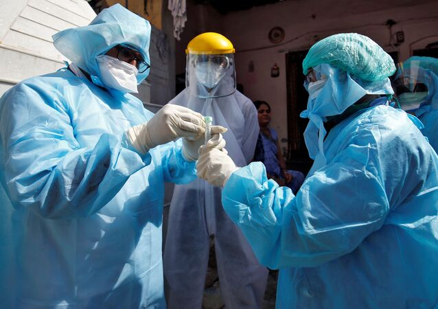 Doctors wearing protective gear seal a vial after taking a swab from a woman to test for coronavirus disease (COVID-19) at a residential area in Ahmedabad, India, April 9, 2020