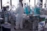 Healthcare workers wearing protective suits attend to COVID-19 coronavirus patients in Barcelona