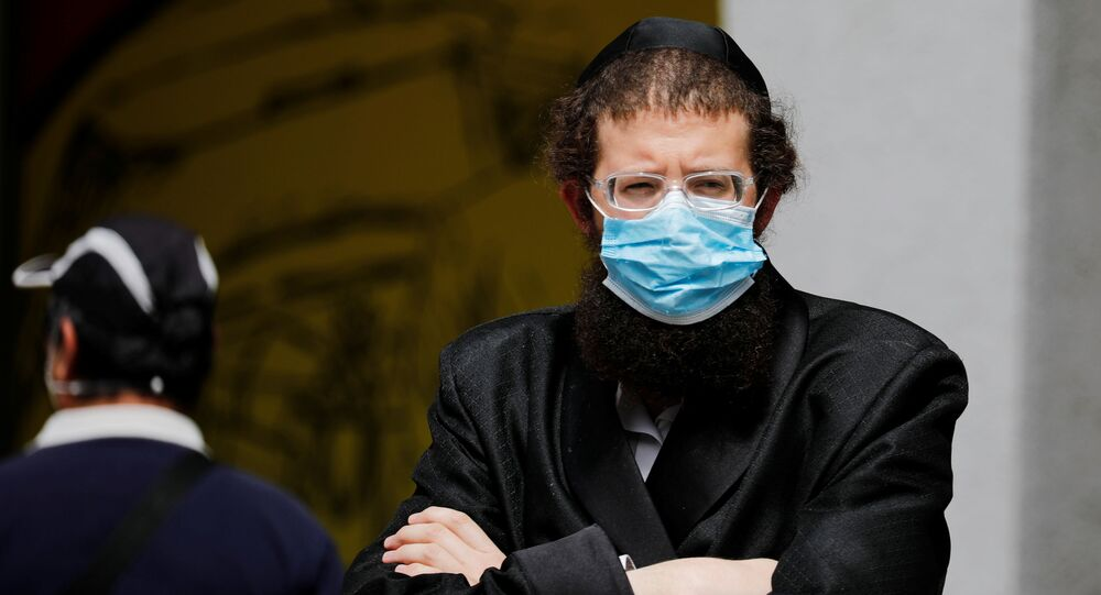 An ultra-Orthodox Jewish man wearing a mask looks on in Bnei Brak, a town badly affected by the coronavirus disease (COVID-19), and which Israel declared a restricted zone due to its high rate of infections, near Tel Aviv, Israel April 5, 2020