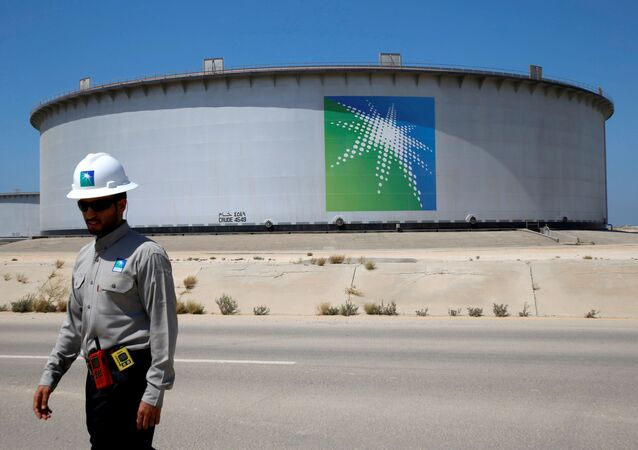 An Aramco employee walks near an oil tank at Saudi Aramco's Ras Tanura oil refinery and oil terminal in Saudi Arabia May 21, 2018