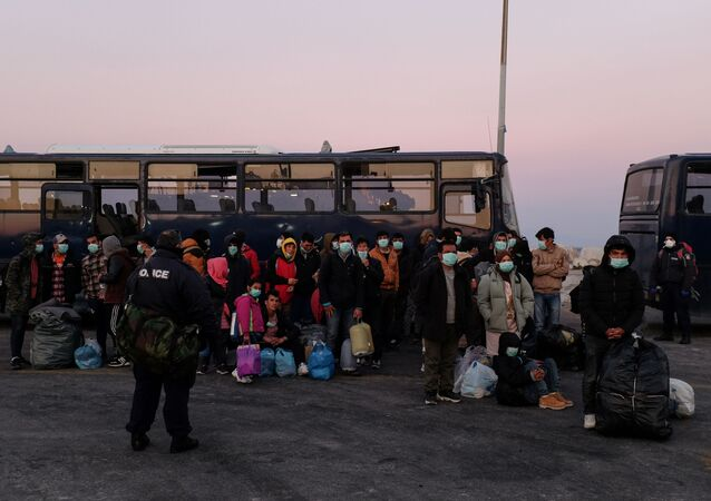 Migrants wearing protective face masks as a precaution against the spread of coronavirus disease (COVID-19), wait to board a ferry that will transfer them to the mainland, at the port of Mytilene on the island of Lesbos, Greece, March 20, 2020