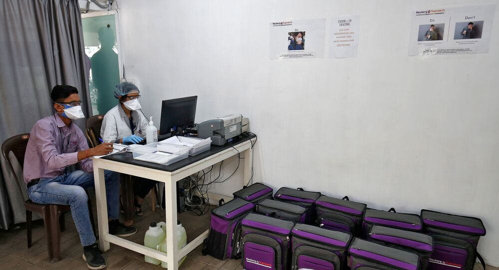 Laboratory technicians sit next to boxes containing coronavirus disease (COVID-19) testing kits at a sample collection centre in Ahmedabad, India March 26, 2020.