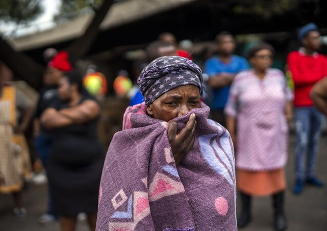 People living near the traditional medicine market wait to receive food baskets from private donors, Monday, April 13, 2020 downtown Johannesburg