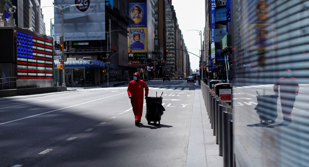 A Times Square Alliance street sweeper worker walks though a nearly empty Times Square in Manhattan during the outbreak of the coronavirus disease (COVID-19) in New York City, New York, U.S., April 7, 2020.