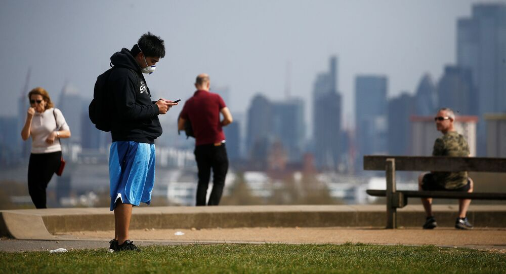 A man wearing a face mask looks at his phone on Primrose Hill in London
